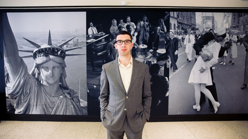 Alex Fitzpatrick stands in front of a photo of the Statue of Liberty and of the nurse kissing a sailor at port at the TIME magazine headquarters.