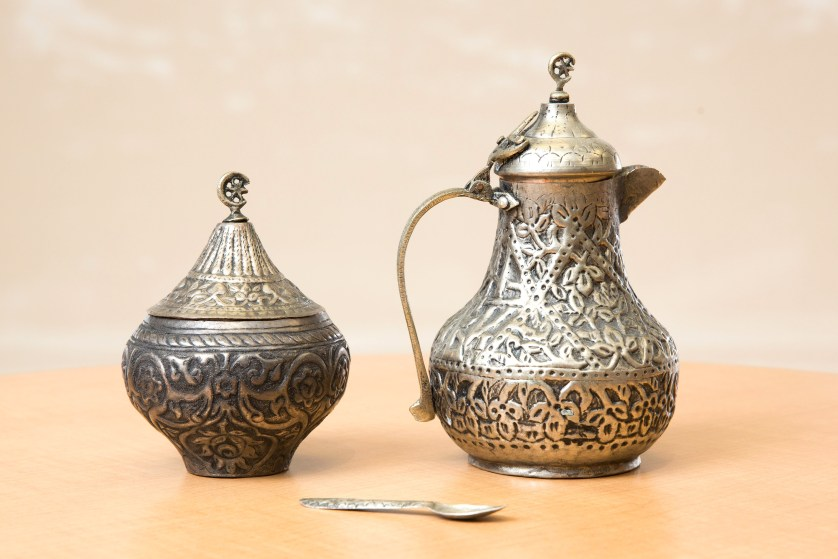 A silver tea set, including a teapot and spoon, from Yugoslavia.