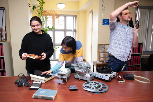 Three students look at film reels and other old high-tech as they try to identify what it is.