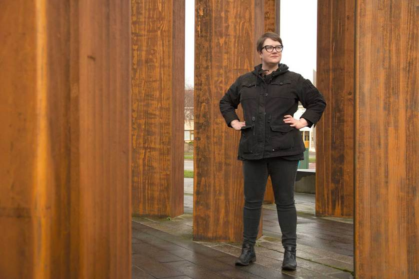 Bizzy Coy in front of a DCU sculpture