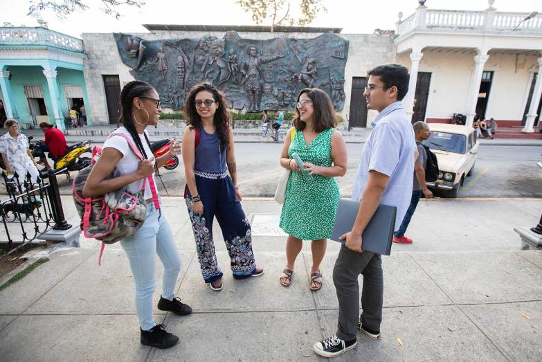 A professor speaks with students in Cuba.