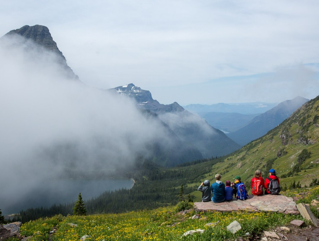 A group of people watch the clouds roll in over the peaks near Logan Pass, Glacier National Park -- what a perfect spot for an adventure elopement!