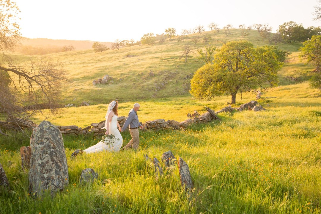 A bride and groom walk through green grass and rolling foothills of the Sierra Nevada during their intimate wedding.