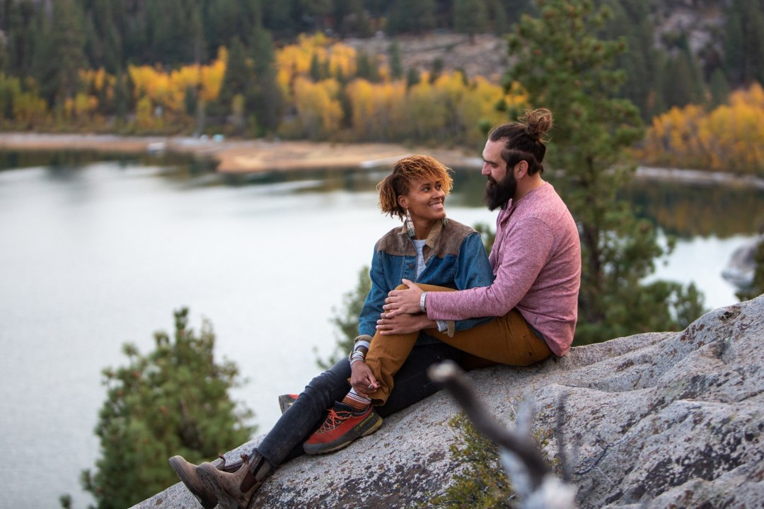 Couple posing at a lake with fall colors for an Adventure Session with Scenic Vows.