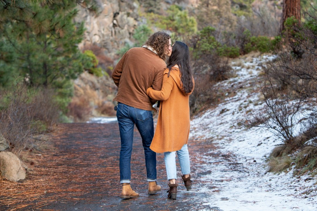 Couple walking, stop to kiss on snow covered path