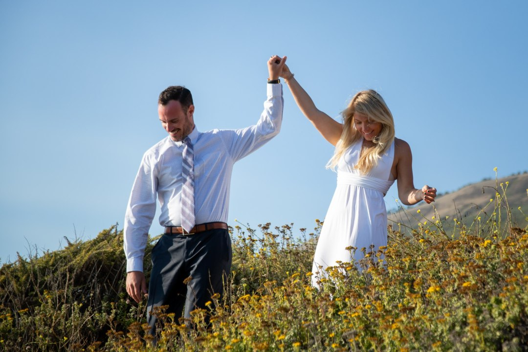 Groom is leading his bride down to the beach for an epic elopement in Big Sur.