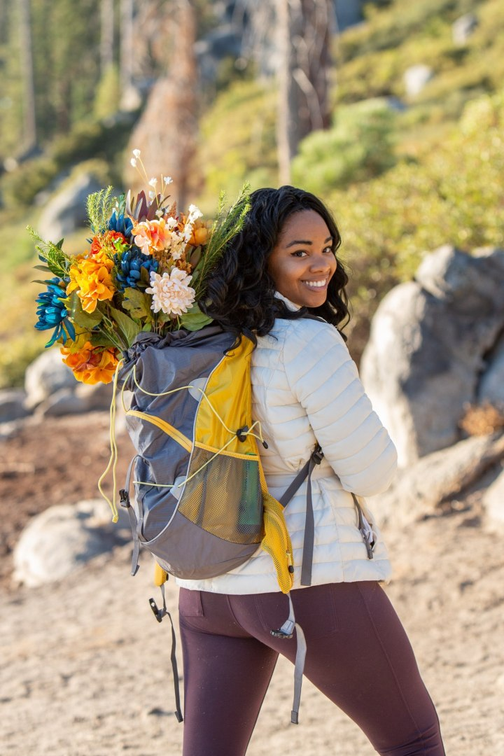 Bride wearing a white jacket and maroon yoga pants, carries a yellow backpack with her wedding bouquet for her elopement