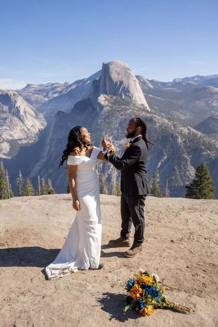 A couple sipping champagne for their Yosemite elopement with Half Dome in the background