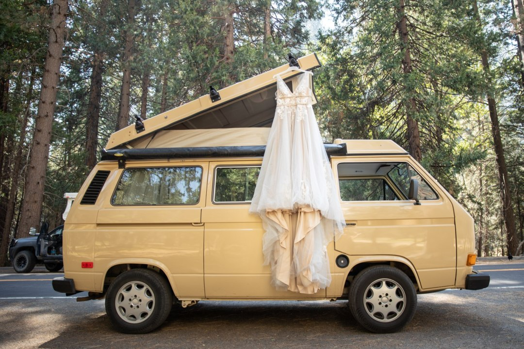 Wedding dress hanging from the top of a VW van.