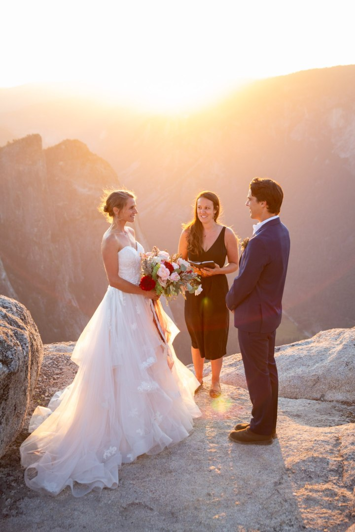 Bride and groom face each other while officiant stands behind them