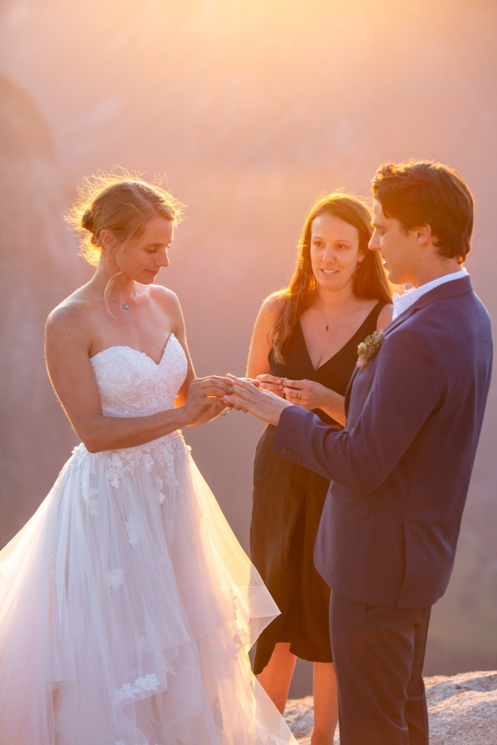 Bride puts ring on grooms finger while repeating vows after officiant