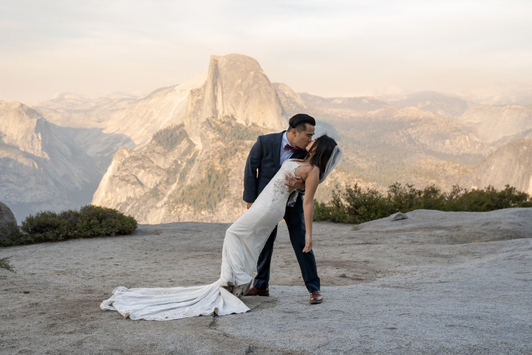 Groom dips his bride with the sunset falling behind on the Yosemite Valley