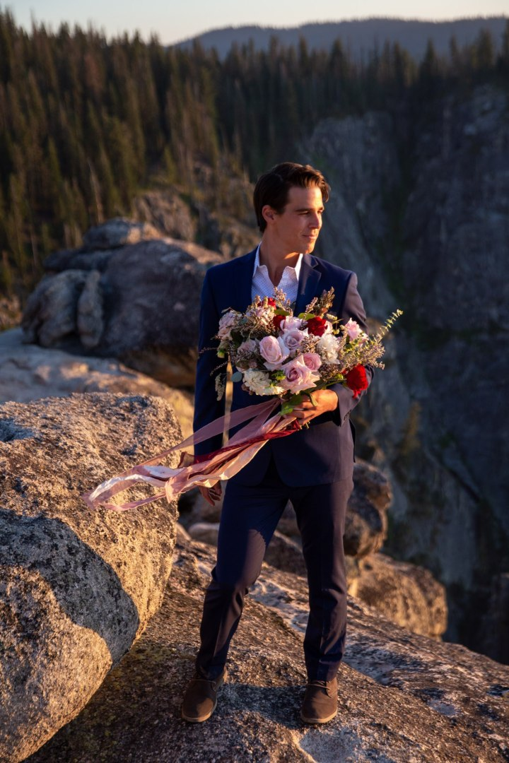 Groom in his blue suit, holding the bouquet of flowers and looking over his left shoulder