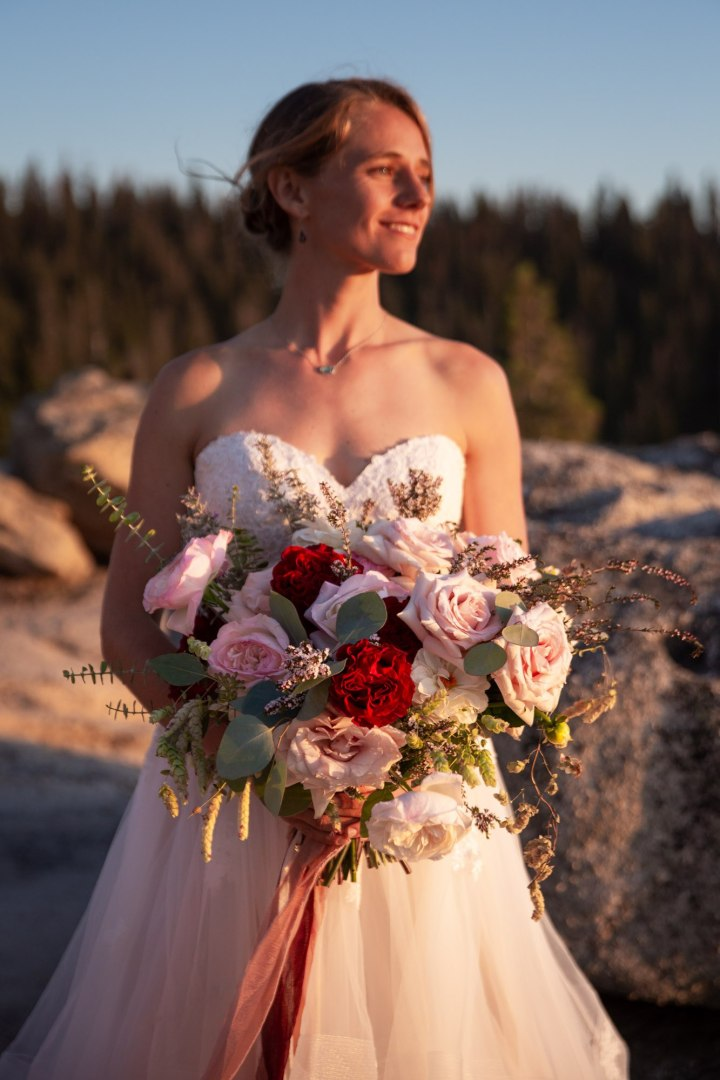 Bride smiling and holding the bouquet of flowers, looking over her left shoulder