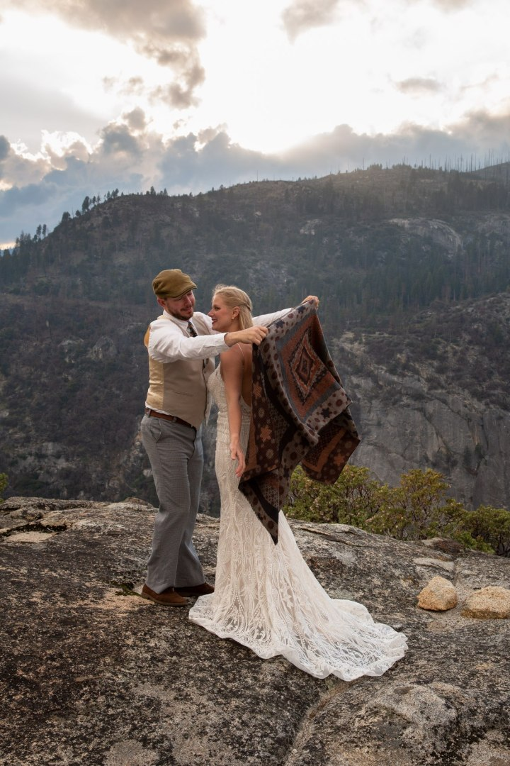 Corey helps Tina with her shawl after their intimate elopement in Yosemite.
