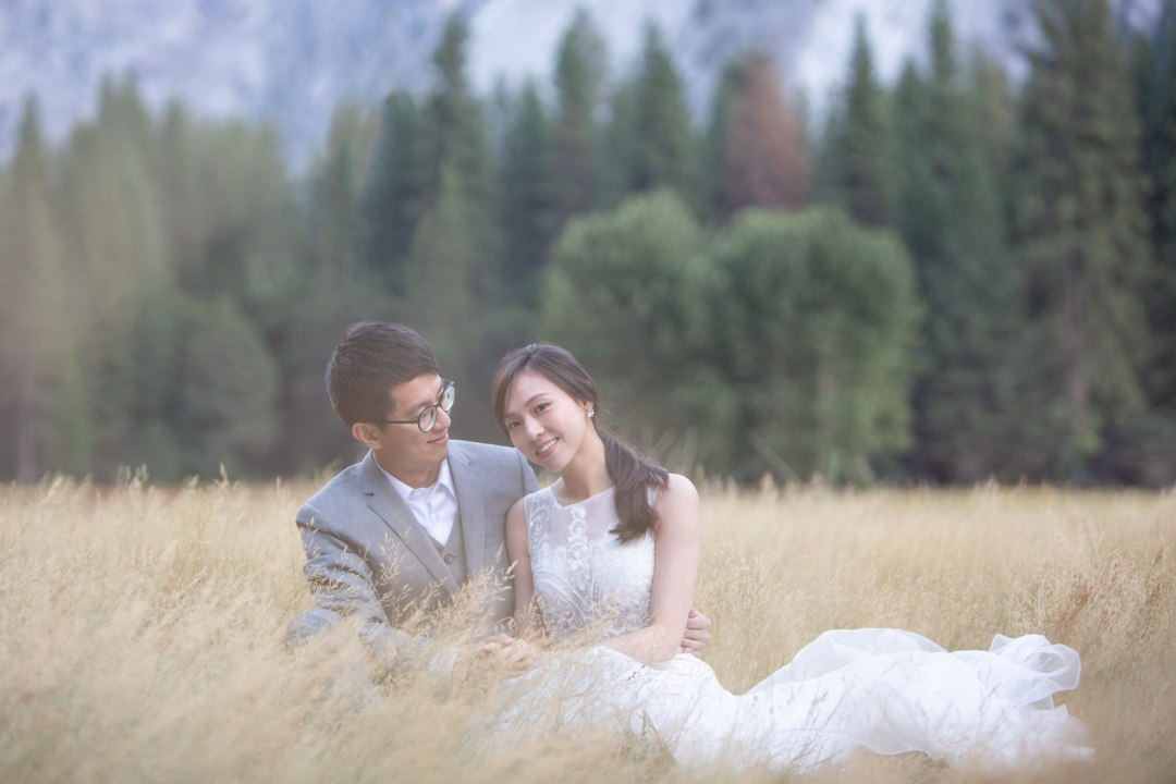 Couple sitting on a trail in a meadow after their Yosemite elopement.
