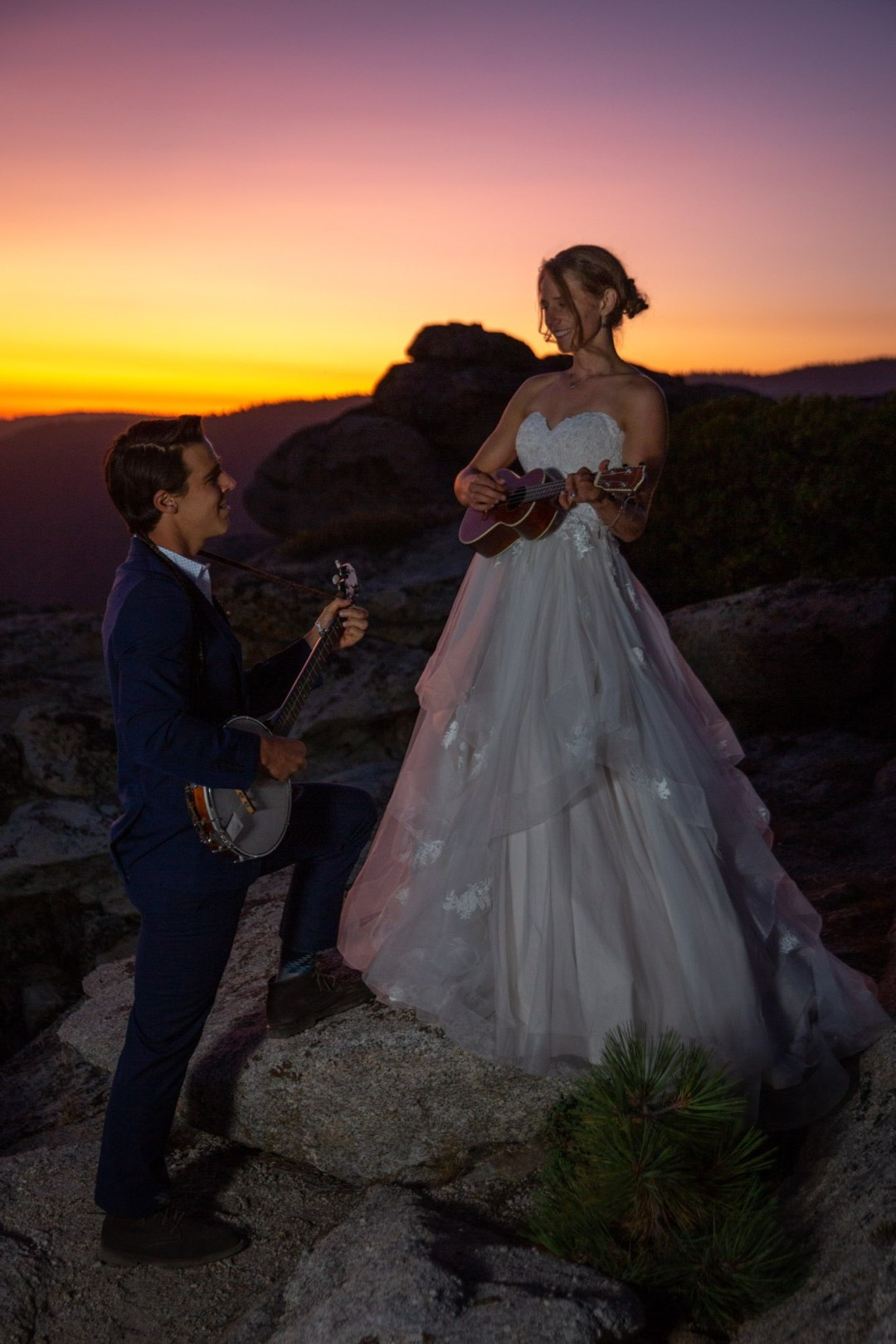 Bride plays ukulele while groom plays banjo as the sun sets