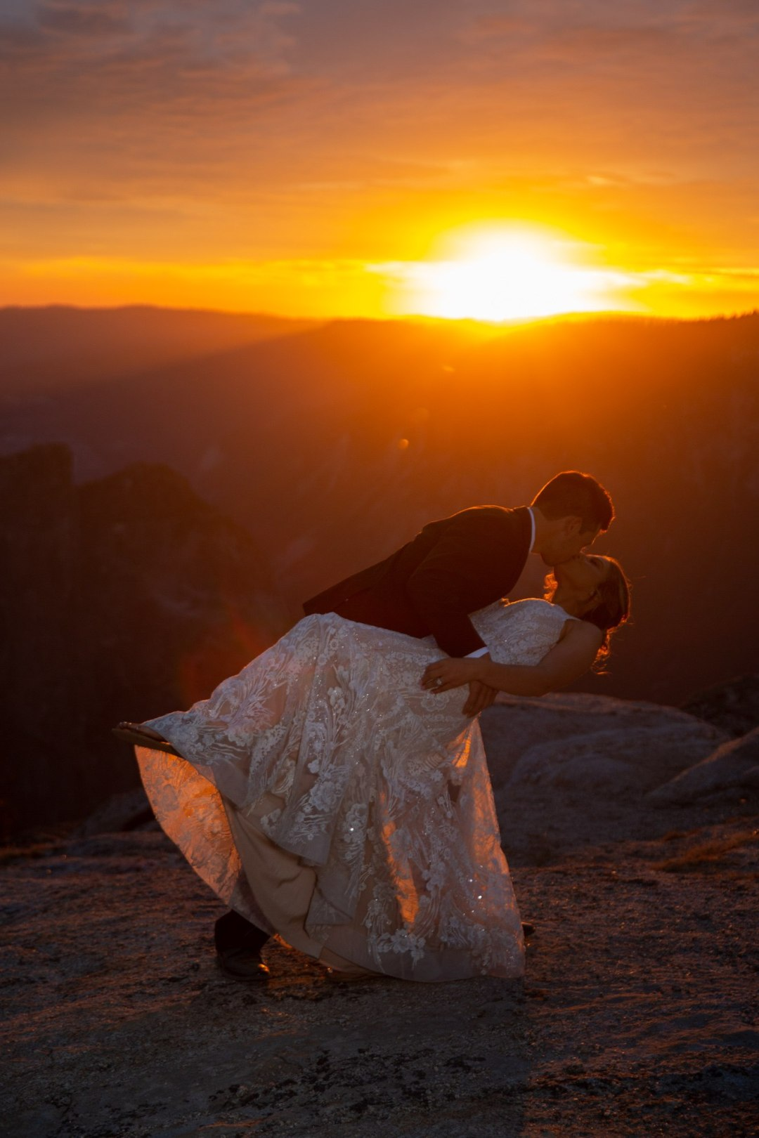 bride and groom dip and kiss in this insane golden sunset on Taft Point