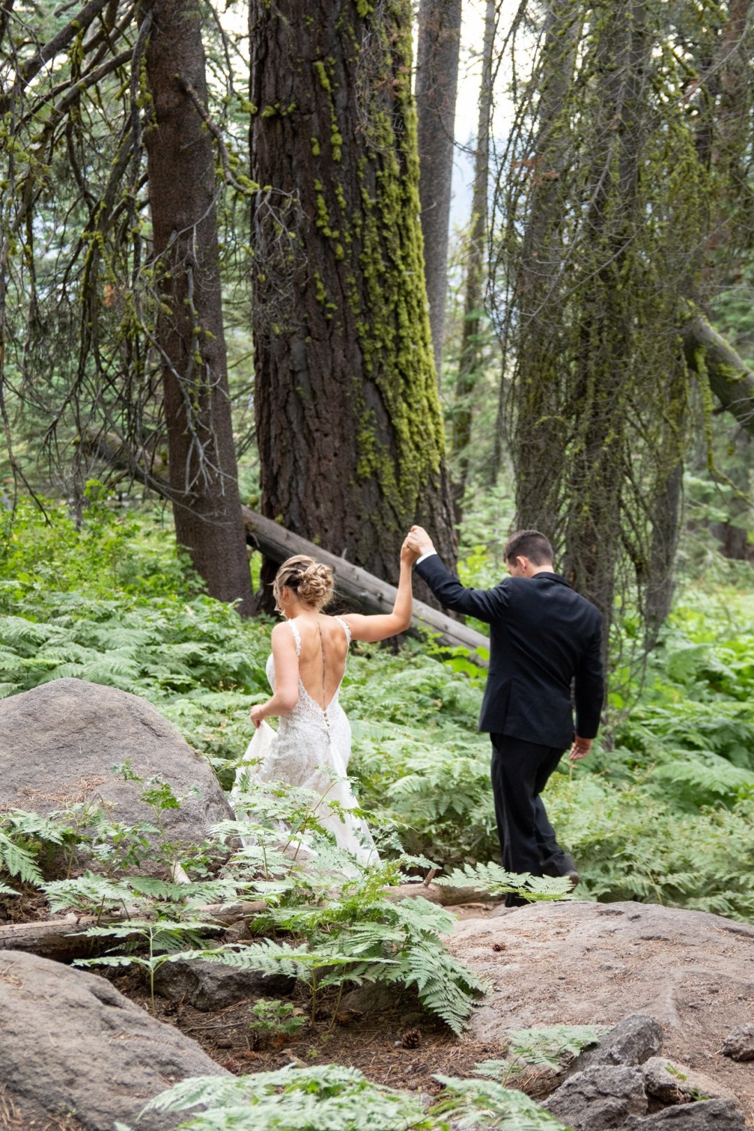 Bride and groom hiking through the ferns and forest on the way to Taft Point