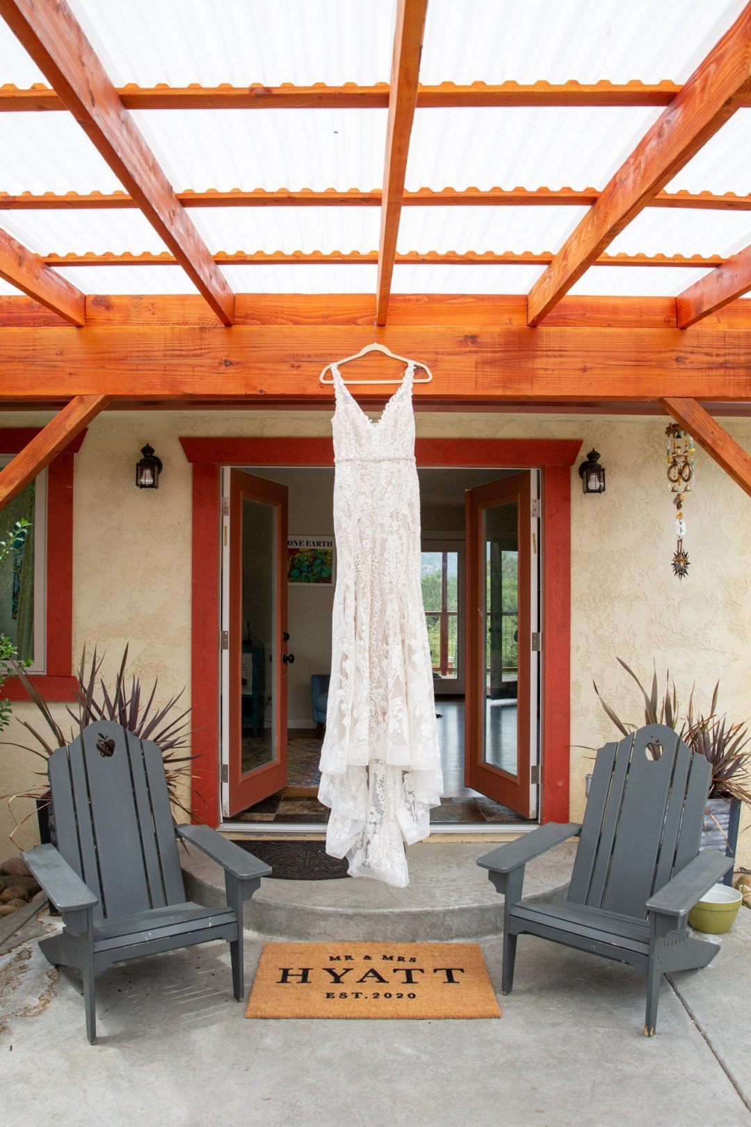 Wedding dress hanging in front of door while bride gets ready.