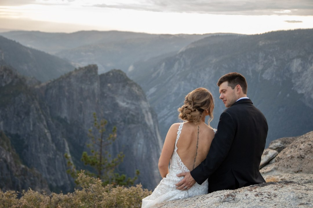 Newlyweds  sitting on a ledge after a sunset Yosemite Elopement.