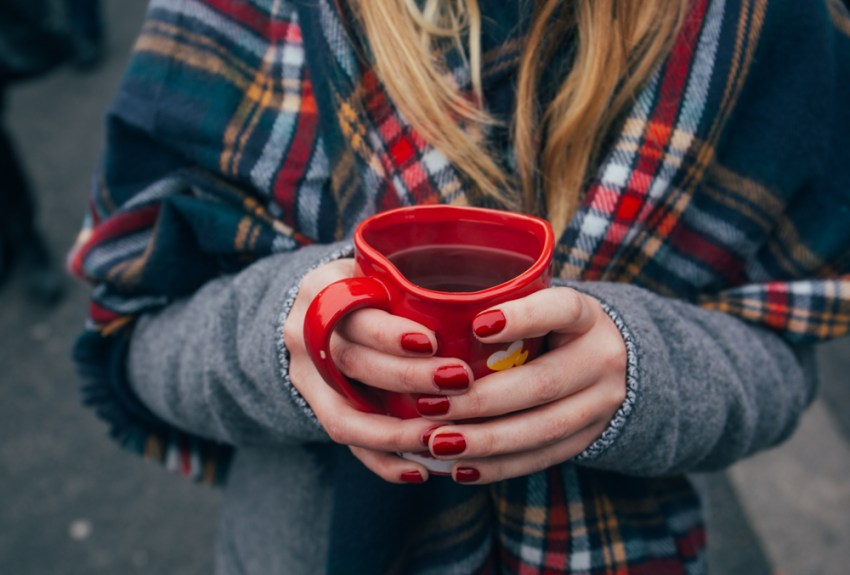 person holding a warm cup of coffee in heart mug