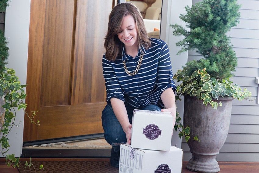 photo of woman picking up her Scentsy boxes from her door step