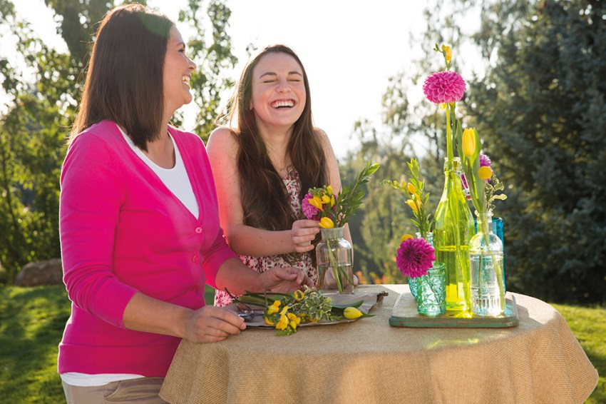 Photo of women creating floral arrangements laughing and having fun