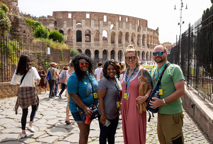 consultants pose and smile on in front of the colosseum in Rome, Italy