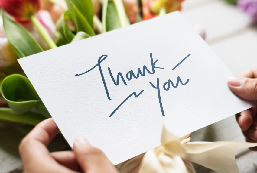 woman holding open a thank you card