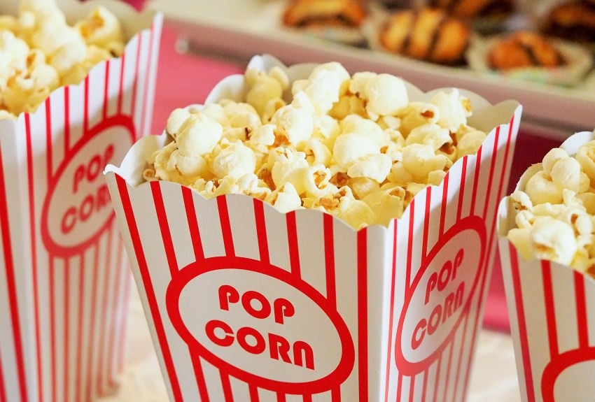 Photo of popcorn and treats atop a table ready for movie night