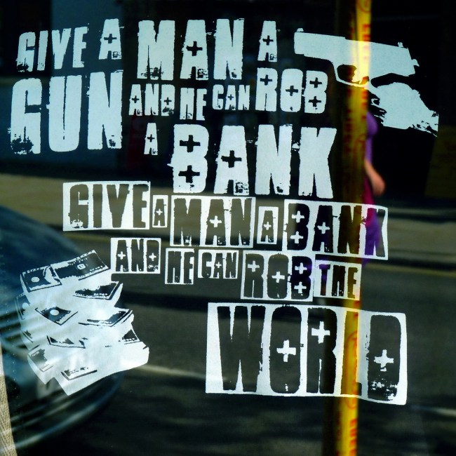 Poster: Give a man a gun and he can rob a bank, give a man a bank and he can rob the world,