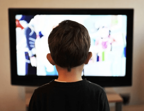 A small boy sits motionless staring at the screen
