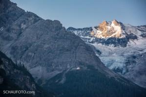 Die Berglhütte leuchtet in der grauen Felswand des Ortlermassivs.