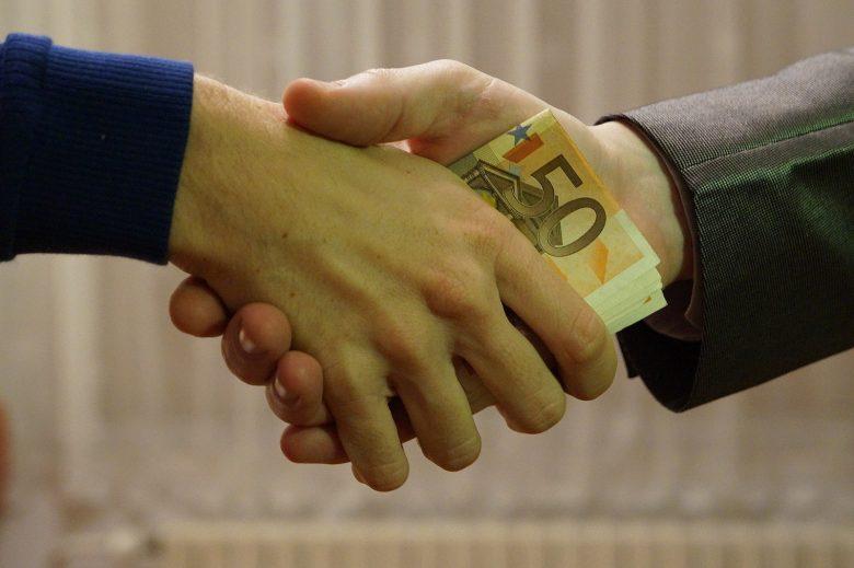 Money being passed between hands in a handshake