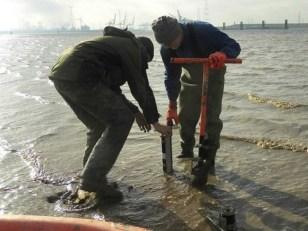 De medewerker van het Waterbouwkundig Lab boorde een gat waarin de sedimentatiemeter past.