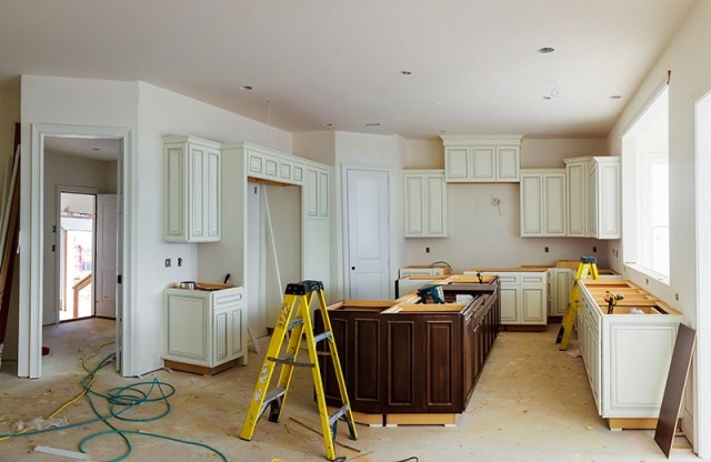 Installation of kitchen. Custom kitchen cabinets in various stages of installation base for island in center