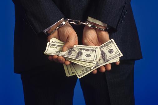 man handcuffs holding hundred dollar bills