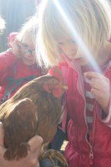 Maja und Alexandra streicheln das Huhn