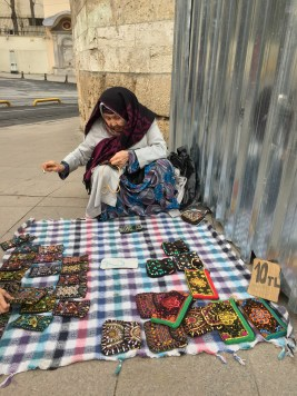 Istanbul Old Lady Street Seller Sewing Her Handmade Pouch with her workpieces