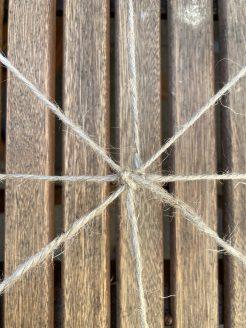 Auf dem Grundnetz von vier gekreuzten Fäden wird reihum gewebt.
