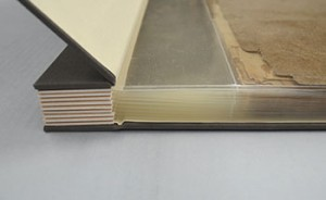 Acid free spacers are placed between some of the sections to make the spine the same width as the text block and a large margin is created on the spine edge to create a larger allowance for the pages to drape as the scrapbook is opened