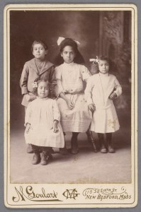 """""""Three girls in dresses and bows in their hair, one little boy,"""" Robert Langmuir African American photograph collection."""