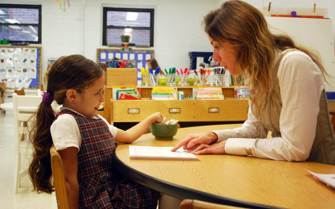 A kindergarten students dictates her story to the teacher.