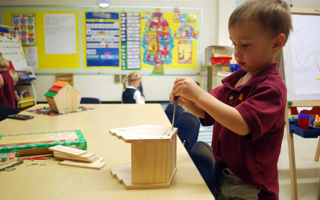 A PreK students works on creating a model home during project week.
