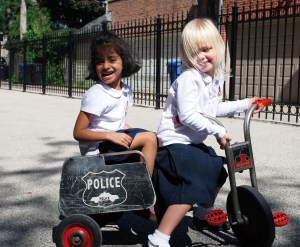 Early childhood students riding bikes on the playground.