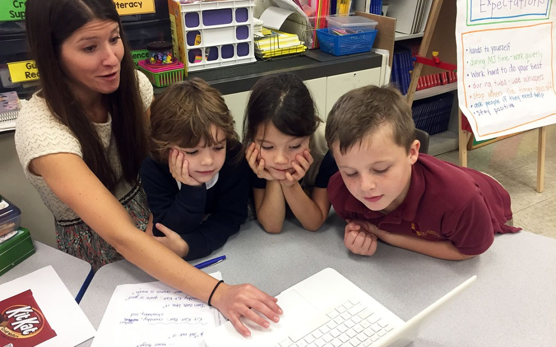 first grade students using a computer with their teacher.