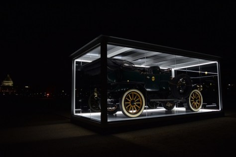 "The car in its lit 'jewel box"" on display on National Mall at night."