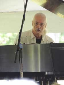 Bill Meyer, pianist from Dave Tatrow Dixie, performs a solo for a crowd in the yellow tent outside the VisTaTech Center