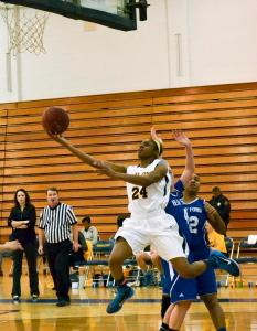 PHOTO BY MIRANDA MALEC STAFF PHOTOGRAPHER Freshman guard T'era Nesbitt attempts an acrobatic layup around two Henry Ford defenders on Feb. 14. Nesbitt has averaged 14.6 PPG this season and has evolved into a top threat for the Ocelots.